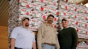 Larry French (center) is flanked by his sons Barrett (left) and Justin (right) in front of pallets of spelt seed.