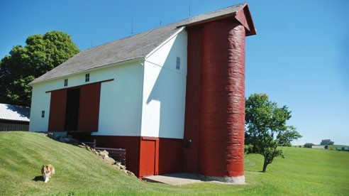 The centerpiece of the farm is its barn featuring a wooden silo constructed from bent Cyprus. The Martins' many buildings add to the tidy farm's historical charm.