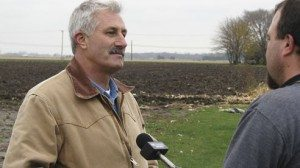 "Cabbage farmer Daryl Knipp talks to a television reporter about the ""Farmers Feed Our Needs"" project."