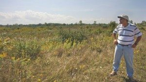 Imed Dami stands where developers plan to put in a large vineyard and winery.