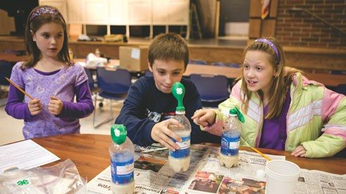 "Meghan Bell, Matthew Strunk, and Madison Huelskamp are excited to see one of their balloons start to inflate while doing a 4-H ""Biofuel Blast"" experiment, which taught students how cellulose and sugars in plants can be converted into fuel."