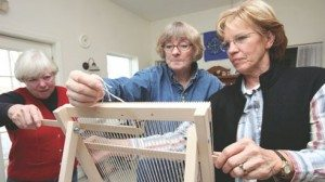 Fiber is weaved on a loom. Left (l to r) Ann Houser, Cindy Shipp and Judy Keske discuss a project.  Members of the Ohio Natural Fiber Network meet monthly to exchange ideas, promote their products and learn about the fiber industry.