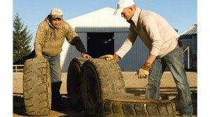 Alan (l) moves tires with son-in-law Derreck Dillon.
