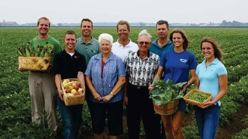 The Michael Family: Front row, L to R; Kyle, Phyllis, Doug, Megan, and Kathy Michael; Back row, L to R; Josh, Todd, Scott, and Kurt Michael. They are standing in front of what amounts to 750 acres of green beans Ohioans can enjoy.