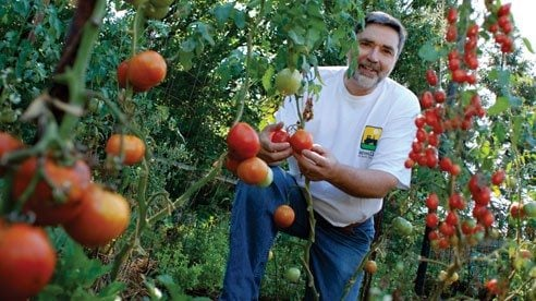 Bill Johnson raises dozens of varieties of fruits and vegetables in his large backyard garden near Columbus.