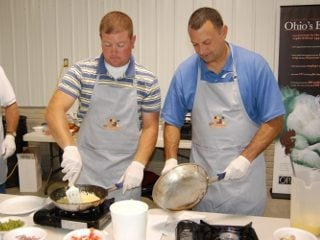 Farm Bureau member Jake Wolfinger (left) and Chamber member Steve Wells (right) make omelets for Ag Update participants.