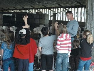 Farmer John Price answers students' questions about raising pigs.