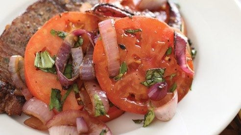 Who said salads have to be green? This one combines smoky onions with the juicy goodness of tomatoes and undoubtedly serves as a wonderful accompaniment to a grilled steak.