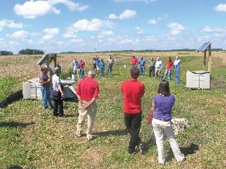 Agricultural organizations learn about equipment used to test the water leaving a field tile on Terry McClure's farm.
