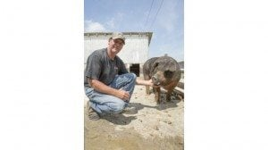 Mike Schumm poses with one of his sows.