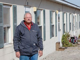 Bruce Buurma stands outside the apartments he provides to migrant workers.