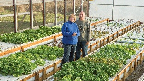 Jeni and Doug Blackburn stand inside their growing structure that allows them to produce greens year-round.