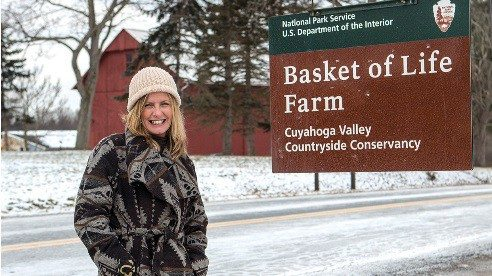 Tracy Emrick stands in front of Basket of Life Farm, one of the 11 farms in the Countryside Initiative farm lease program. Basket of Life Farm operates a CSA and sells at farmers markets.