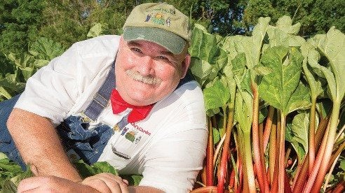 Farmer Lee Jones poses next to a row of Mr. Frye's Rhubarb.