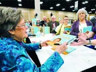 Laurie Krebs signs copies of her book during American Farm Bureau's annual meeting.