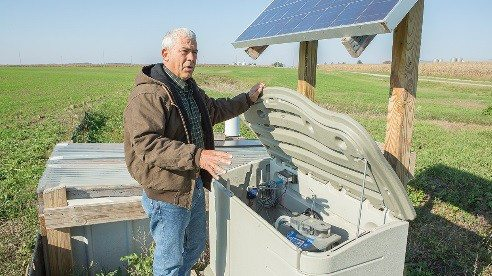Terry McClure explains how researchers are measuring rainwater runoff on his farm as part of a three-year study to determine how much phosphorus it contains.