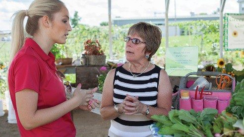 Ohio Farm Bureau Organization Director Ashley Schweiterman (left) talks with Trish Jones at the Green Machine farmers market.
