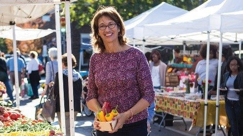 Donita Anderson, executive director of the North Union Farmers Markets, shows off the fall harvest at the Shaker Square location.