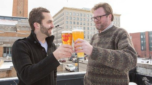 Sam McNulty and Andy Tveekrem raise a glass to The Palace of Fermentation as the Ohio City neighborhood serves as the backdrop.