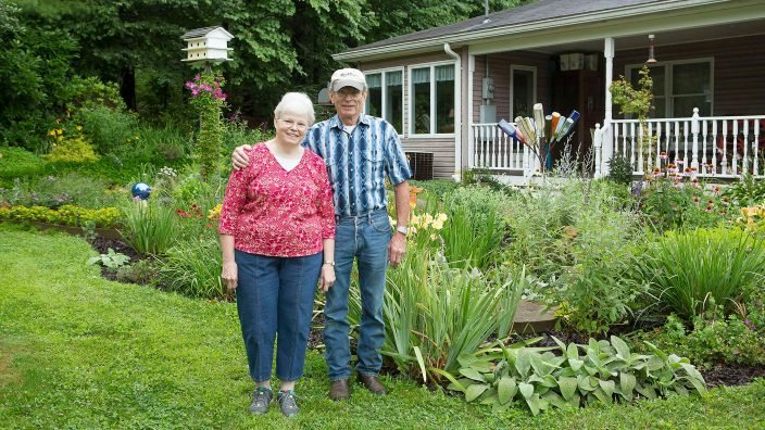 Elderly man and woman standing in front of their property