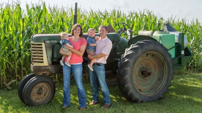 Family standing in front of tractor