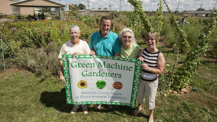 Joyful group of members of the Green Machine Gardeners standing behind signage