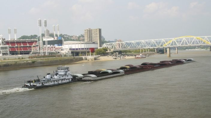 Tug Boat with Barges on the Ohio River.  Barges are empty.  Cincinnati and bridges in the background.