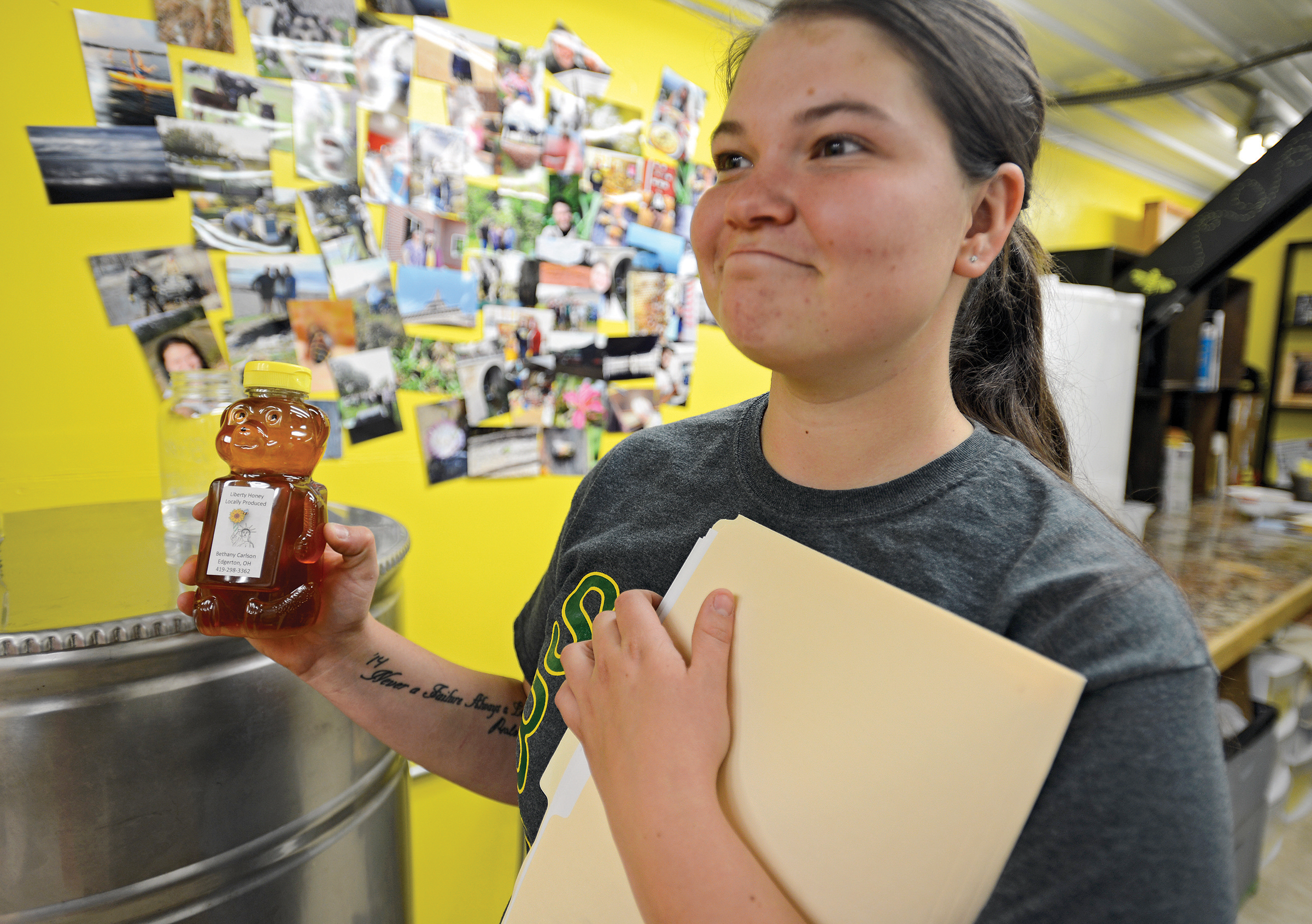 OFB_beekeeper_5859: Apiarist Bethany Carlson, 20, holds a jar of her Liberty Honey, which she produces and sells the hives she maintains on her family's homestead in Edgerton, Ohio, Thursday, June 30, 2016. (Photo by Peggy Turbett)