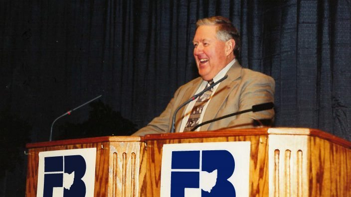 Kenny Walter smiling while giving speech in front of a lectern
