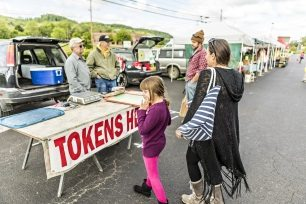 Kaity Grimm and her mother, Jennifer, prepare to shop for produce at the Athens Farmers Market by securing dollar-for-dollar tokens swiped from their Electronic Benefits Transfer card.