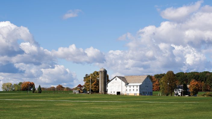 """Farming landscape on a beautiful sunny summer day, good fair weather under high cumulus clouds, wide view of a farm with white barn in Ohio, OH, USA."""