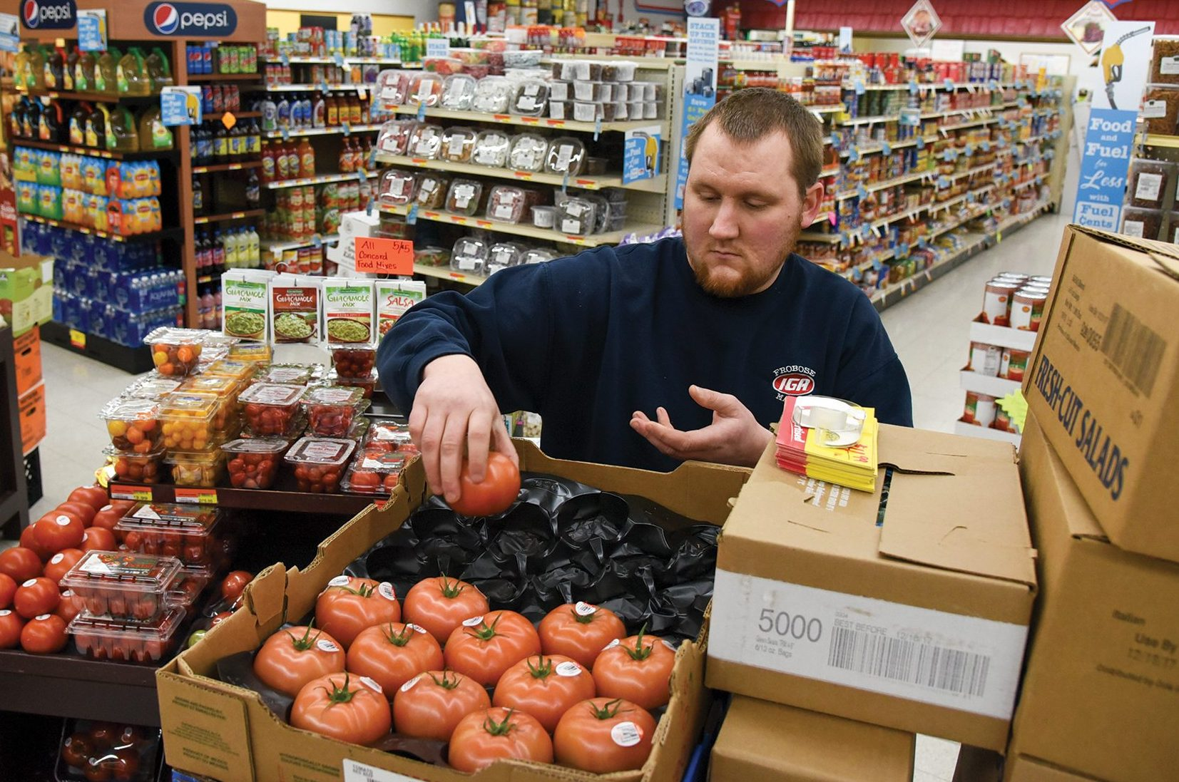 Zach Frobose, produce manager for Frobose Meat Locker, Inc., restocks tomatoes at the family's IGA-affiliated grocery store in Pemberville, Ohio, Monday, Dec. 11, 2017.(Photograph by Peggy Turbett for the Ohio Farm Bureau)