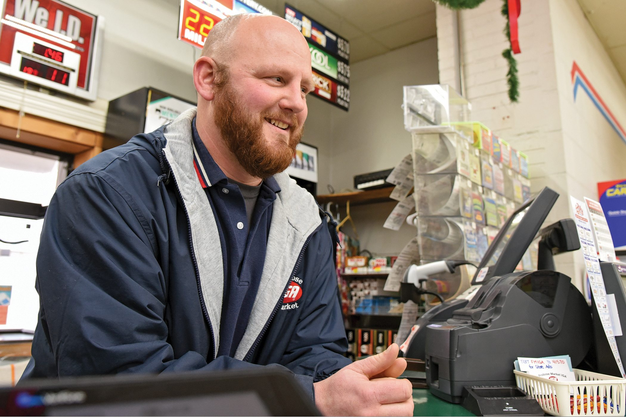Jacob Frobose, Frobose Meat Locker's farm manager, fills in behind the customer service desk at the family's IGA -affiliated grocery store in Pemberville, Ohio, Monday, Dec. 11, 2017. (Photograph by Peggy Turbett for the Ohio Farm Bureau)