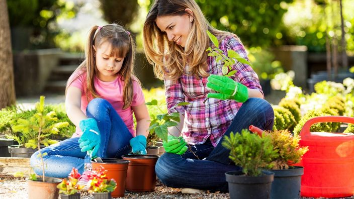 Mother and daughter planting flowers together.