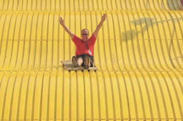 Ohio State Fair general manager Virgil Strickler takes a break from his duties to slide down the fair's iconic giant slide.