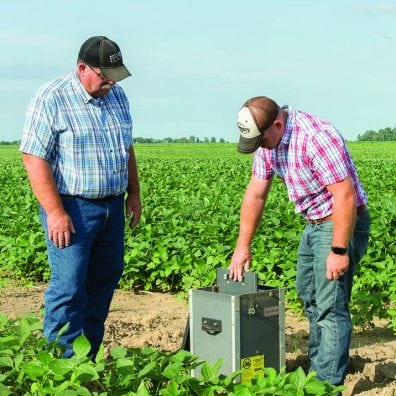 Tim Jackson, left, and son Evan check the water level control structure that helps control nutrient runoff from the field. Plates called stoplogs can be added or removed to adjust water level/flow.