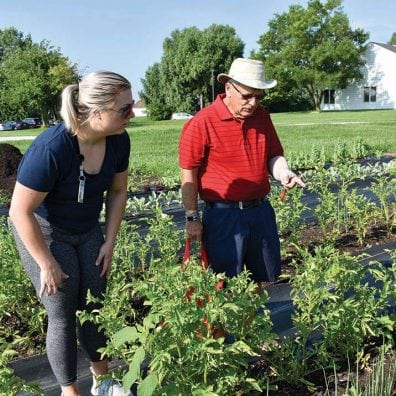 Ohio State University student Monica Schroll helps cancer survivor Ed Price pick out vegetables at the Garden of Hope.